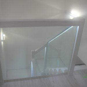 Białe schody dywanowe z szybą i ledami